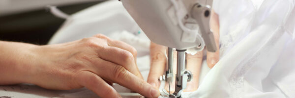 Close up view of sewing process. Female hands stitching white fabric on professional manufacturing machine at workplace. Seamstress hands holding textile for dress production. Light blurred background; Shutterstock ID 1416331862; Purchase Order: -